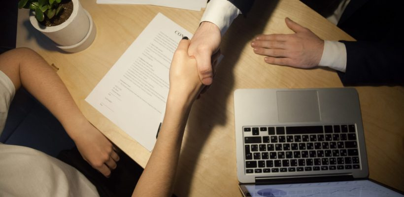 Handshake top close up view. Two businesspeople shake hands to seal a deal, laptop computer with rising stats on the desk. Human resources manager promoting successful employee. Seal a deal concept.
