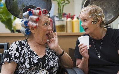 Mature woman with curls and hairclips in head talking at beauty parlor