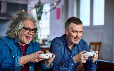 Two men using games consoles, gaming, connection, excitement, interactivity, focus