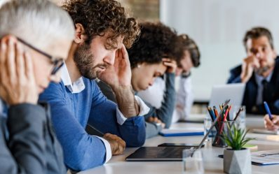 Group of entrepreneurs feeling frustrated during a meeting in the office. Focus is on man with headache.