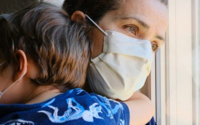 Caucasian Mature woman posing with her son, both with protective masks, very sad looking through window worried about Covid-19 lockdown